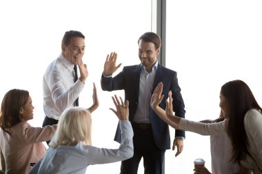 Excited diverse employees giving high five celebrating corporate success