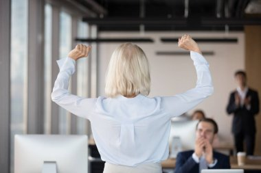 Rear view at middle-aged businesswoman raising hands celebrating business success
