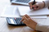 Profesionální žena pomocí kalkulačky pro finanční účetnictví, zblízka