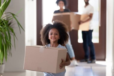 Cute funny african kid girl holding box in new house
