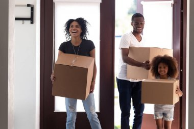 Excited black family entering new house holding boxes moving in