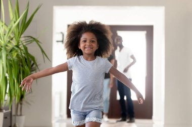 Cute african kid running in new house on moving day