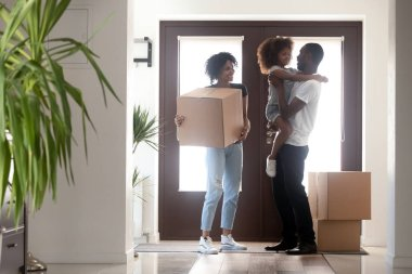Happy black family with kid boxes moving in new house