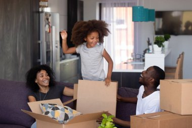Happy mixed-race child jumping out of box playing with parents