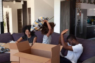 Happy african child enjoy pillow fight with parents packing boxes