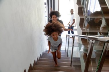 Happy african kid with parents running upstairs into new house