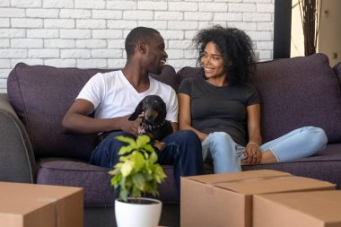 Happy african couple moving into new home with pet boxes