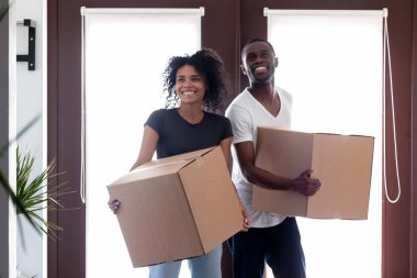 Excited black couple carrying boxes entering big modern house hallway