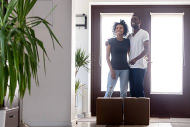 Happy black couple embracing standing in new house with boxes