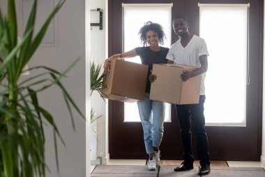 Black couple holding boxes standing in hallway looking at camera