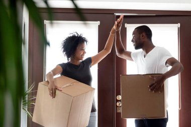 Happy african couple giving high five celebrating moving day