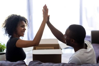 Happy young african tenants couple giving high five celebrating moving