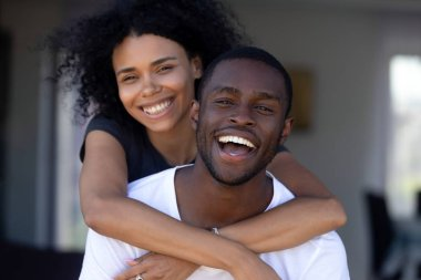 Happy millennial black couple laughing having fun outdoors, portrait