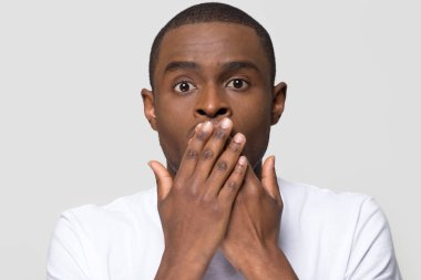 Shocked horrified african man covering mouth with hands feel scared
