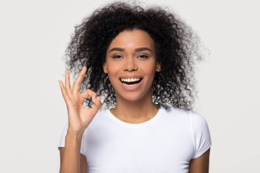 Happy black woman showing ok gesture smiling looking at camera