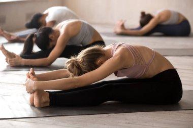 Young yogi practice yoga poses relaxing in studio