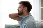 Naštvaná unavený mladý muž cítit bolest masírování ztuhlý krk
