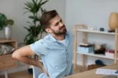 Unavený muž cítit bolest v zádech trpí nižší bolesti zad
