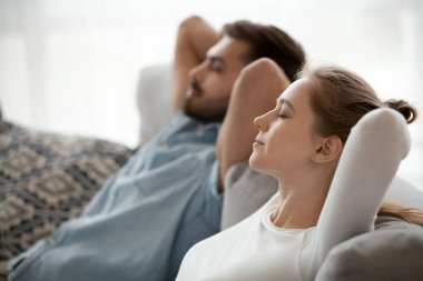 Happy calm couple enjoying relaxation having nap on sofa breathing
