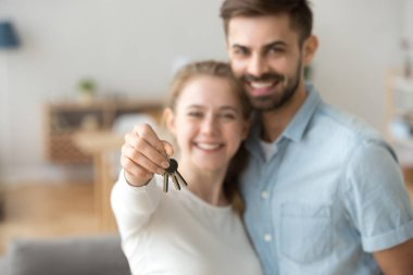 Happy young married family couple holding keys to new flat
