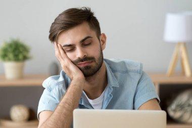 Bored sleepy man feels drowsy resting on hand near laptop