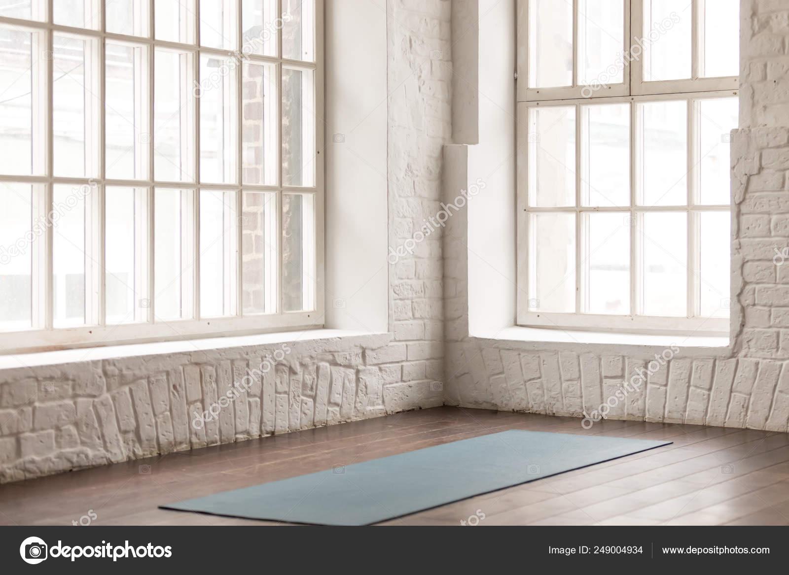 Yoga Mat On Wooden Floor In Empty Room In Yoga Studio Stock Photo C Fizkes 249004934