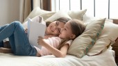 Fotografie Cute child daughter holding book reading to mom in bed