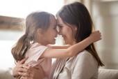 Roztomilé dítě dívka všeobjímající usměvavá maminka dotýká nosy baví