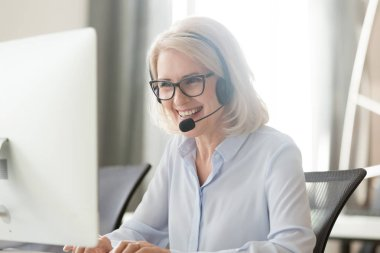 Happy old businesswoman in headset making call looking at computer