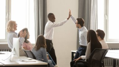 Happy diverse employees giving high five together celebrating shared win