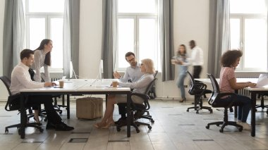 Busy multicultural employees working on computers in modern office rush