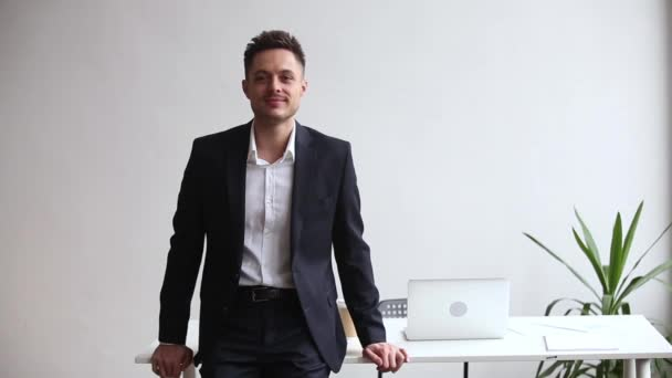 Happy millennial businessman leader in suit posing at workplace, portrait