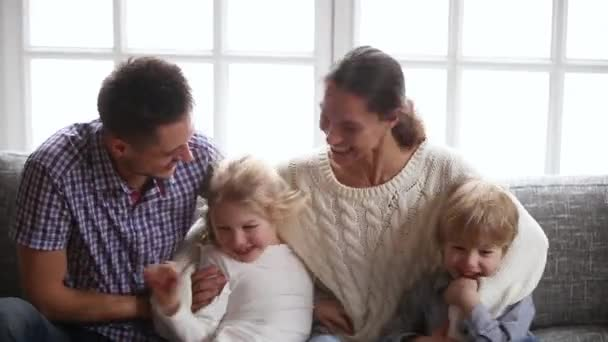 Happy parents with kids having fun laughing tickling on sofa