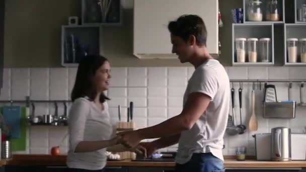 Happy funny romantic couple dancing to music in the kitchen