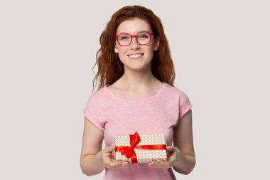 Smiling red-haired girl make present holding gift box