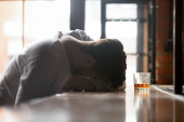 Fotografie Drunk man sleeping on bar counter near glass with alcohol