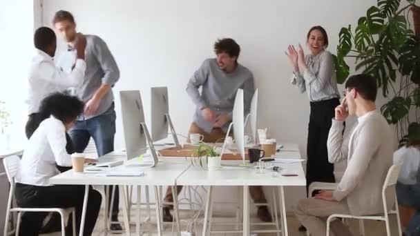 Šťastní různé kancelářské dělníky, kteří se baví házet kuličkami na papír