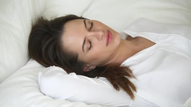 Klidná žena s krásnou tváří dobře spící v pohodlné posteli