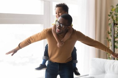 Happy african father piggybacking little son playing together at home