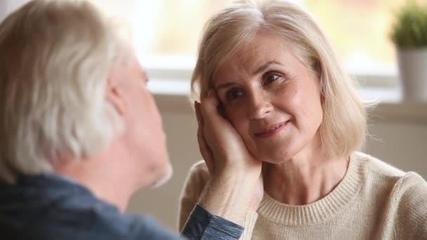 Milující starší manžel hladil tvář staré ženy vyznácí lásku