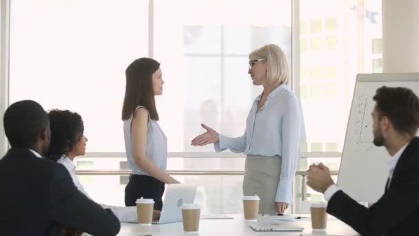 Happy female mature boss handshaking young employee congratulating with promotion