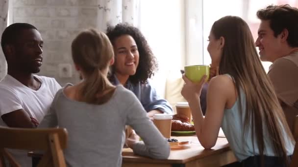 Diverse happy students talking joking having fun share cafe table