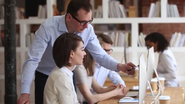 Male mentor executive manager teaching female intern explaining online work