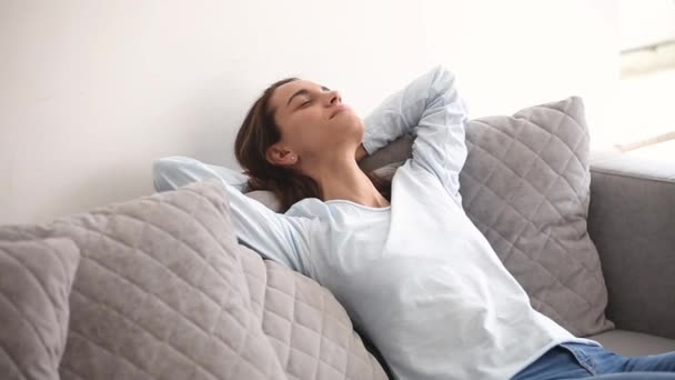 Millennial woman closed eyes resting on comfortable couch at home
