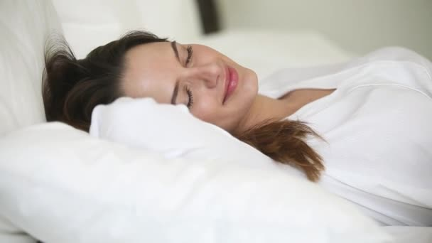 Zavřít tvář spící atraktivní žena ležící na bílých lůžkoviny