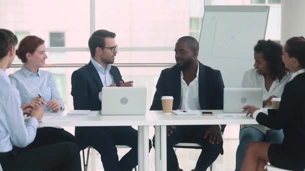 African and caucasian businessmen in suits talking at group negotiations