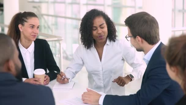 Diverse businesswoman and businessman make deal handshaking at group meeting