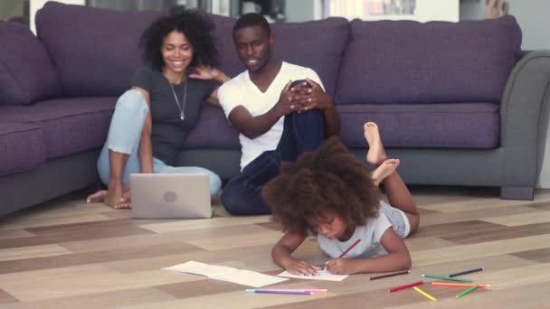 Dětská holčička na teplém patře s šťastným černým rodičem