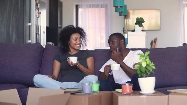 Šťastný africký pár popíjení kávových krabic v novém domě