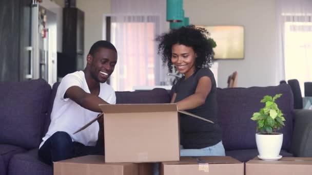 Happy black couple unpacking box or parcel discussing interior design